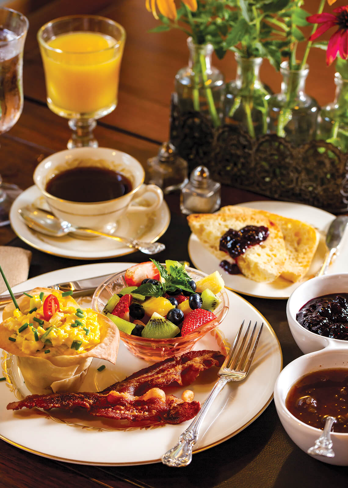 An elaborate breakfast meal with eggs, bacon and fruit.