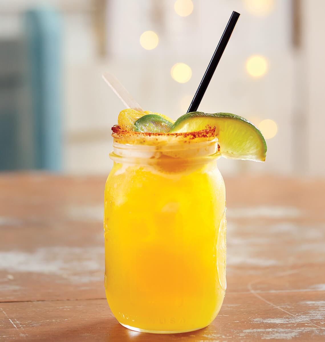 Fancy cocktail in a mason jar with fruit garnish.