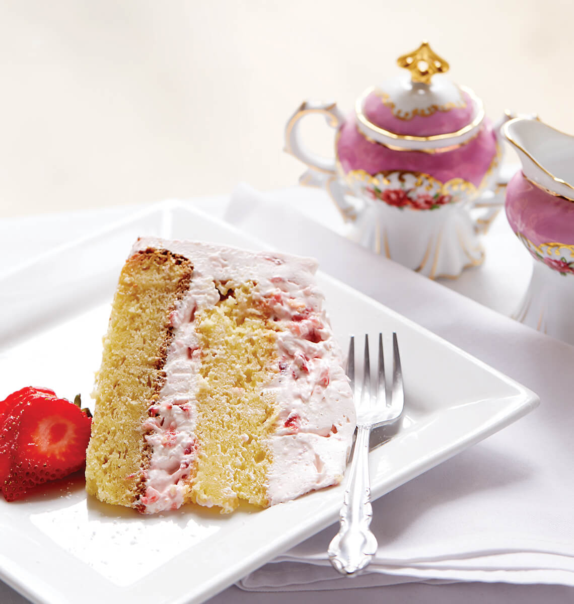A piece of cake on a plate with tea pitcher.
