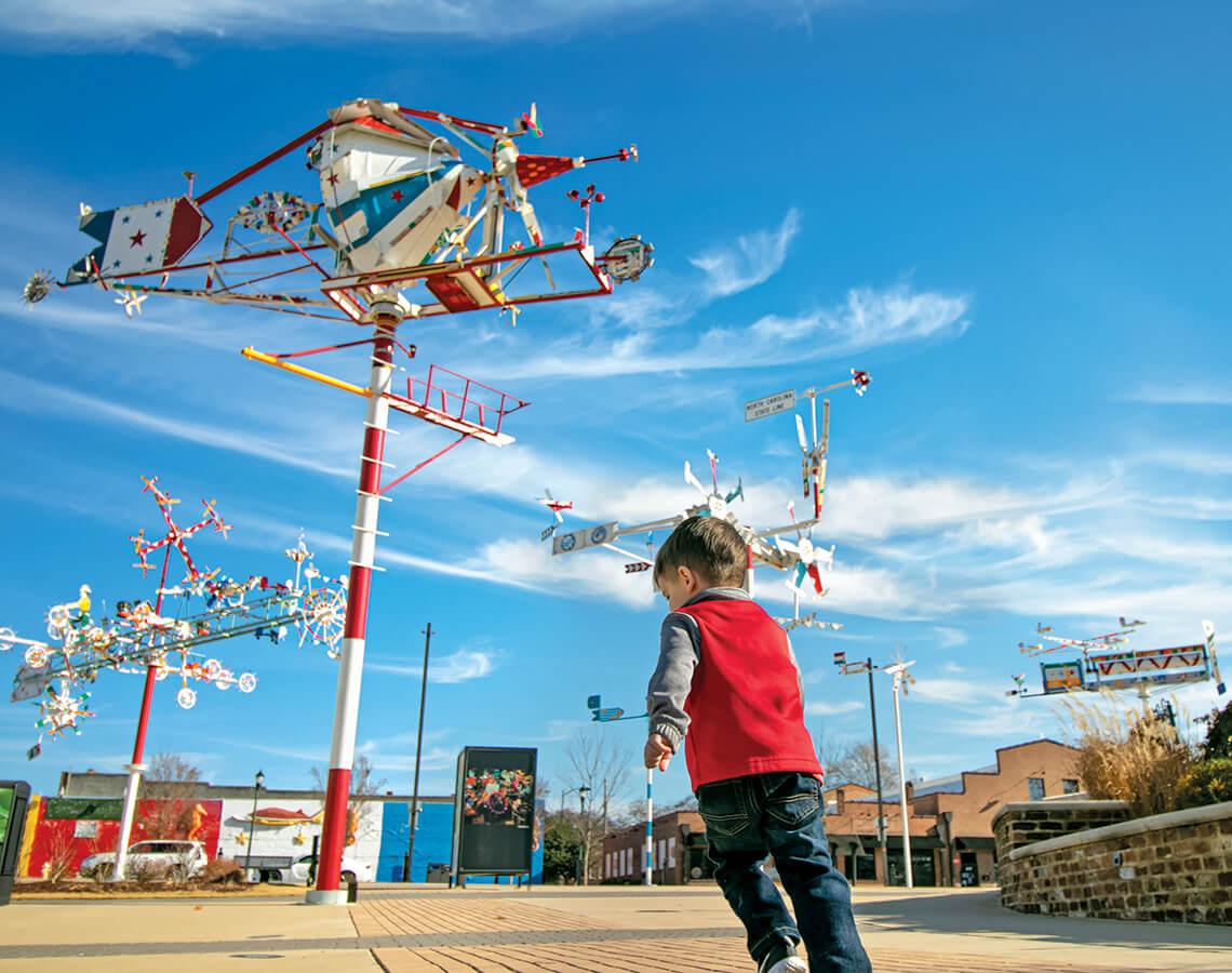 Children play beneath the whirligig Time Machine.