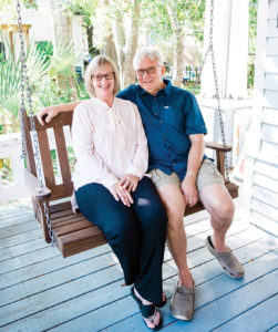 Debbie & Ricky Evans sit on swinging chair of porch.