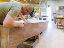 Student uses planer to shape boat trim.